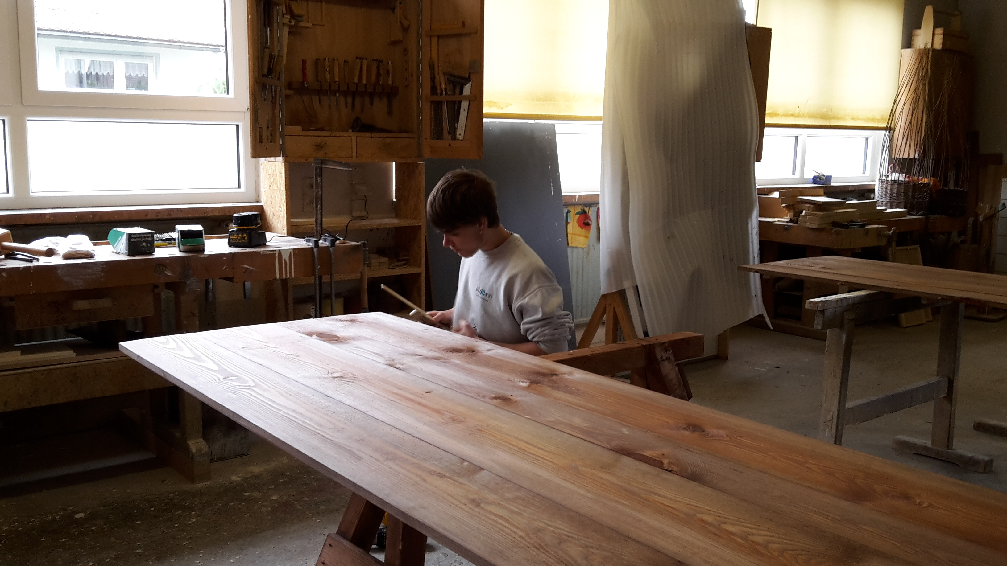 Marcel in der Schreinerei hoch konzentriert beim Bohren der Dübellöcher