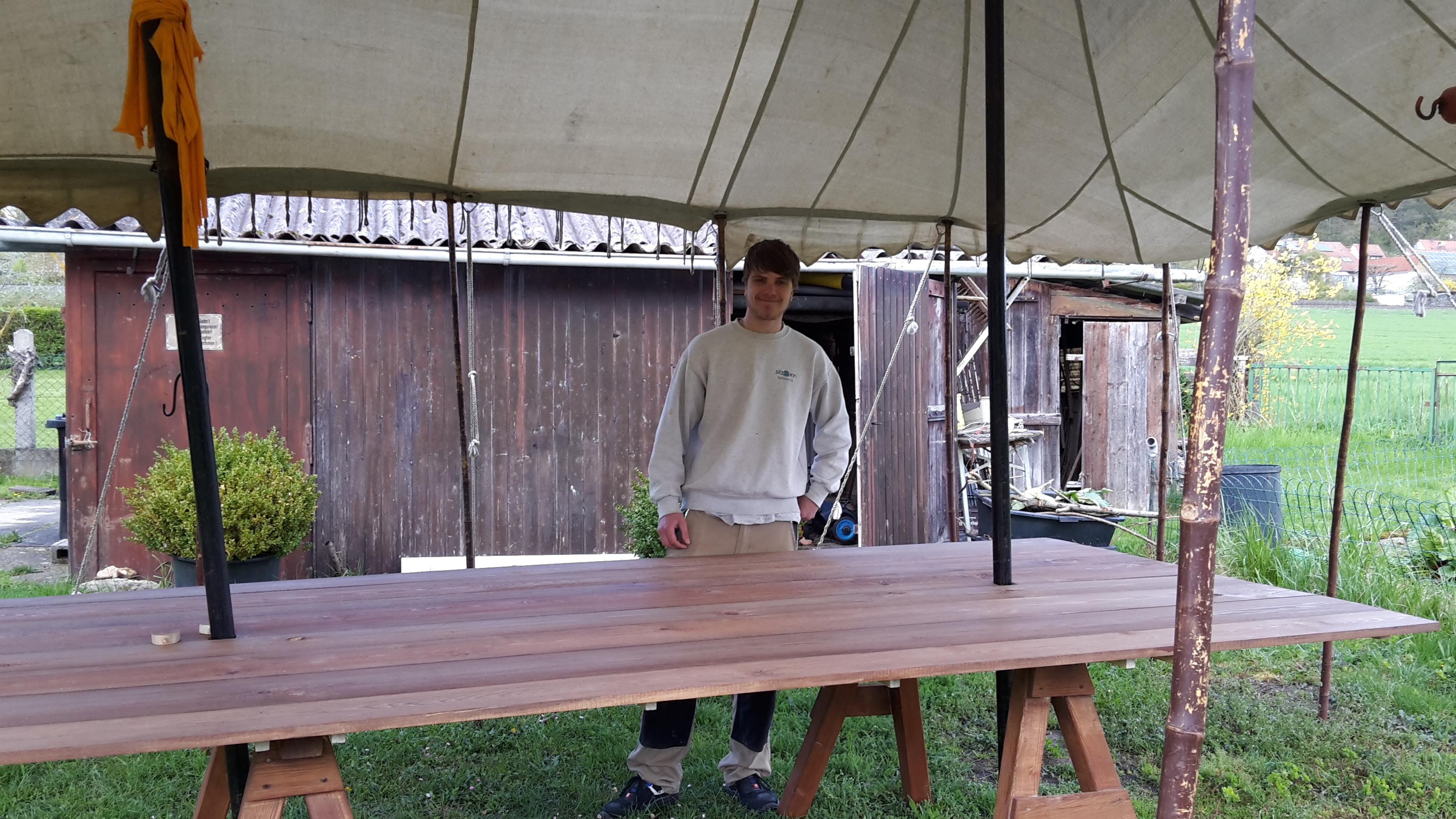 Marcel in der Schreinerei vor dem fertigen Münzertisch unter dem Baldachin